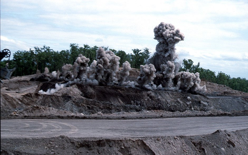 Clouds of dust rise as blasting occurs at mine