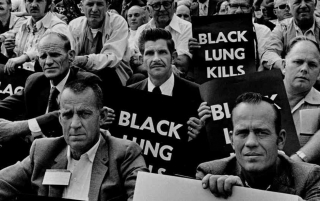 Coal miners hold Black Lung Kills posters during a protest