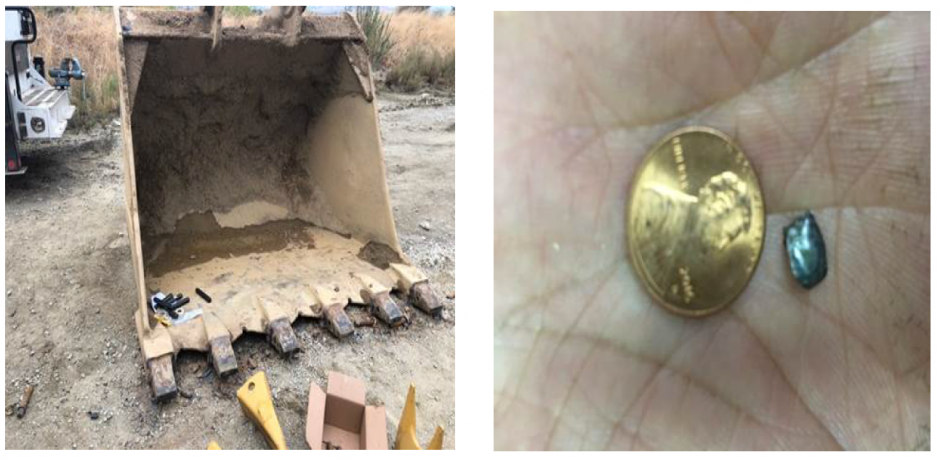 excavator bucket on left and small piece of metal smaller than penny on right