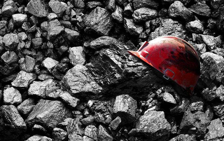 A worker's safety helmet sitting on top of mined material.