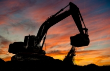 An active backhoe working on site as the sunsets.