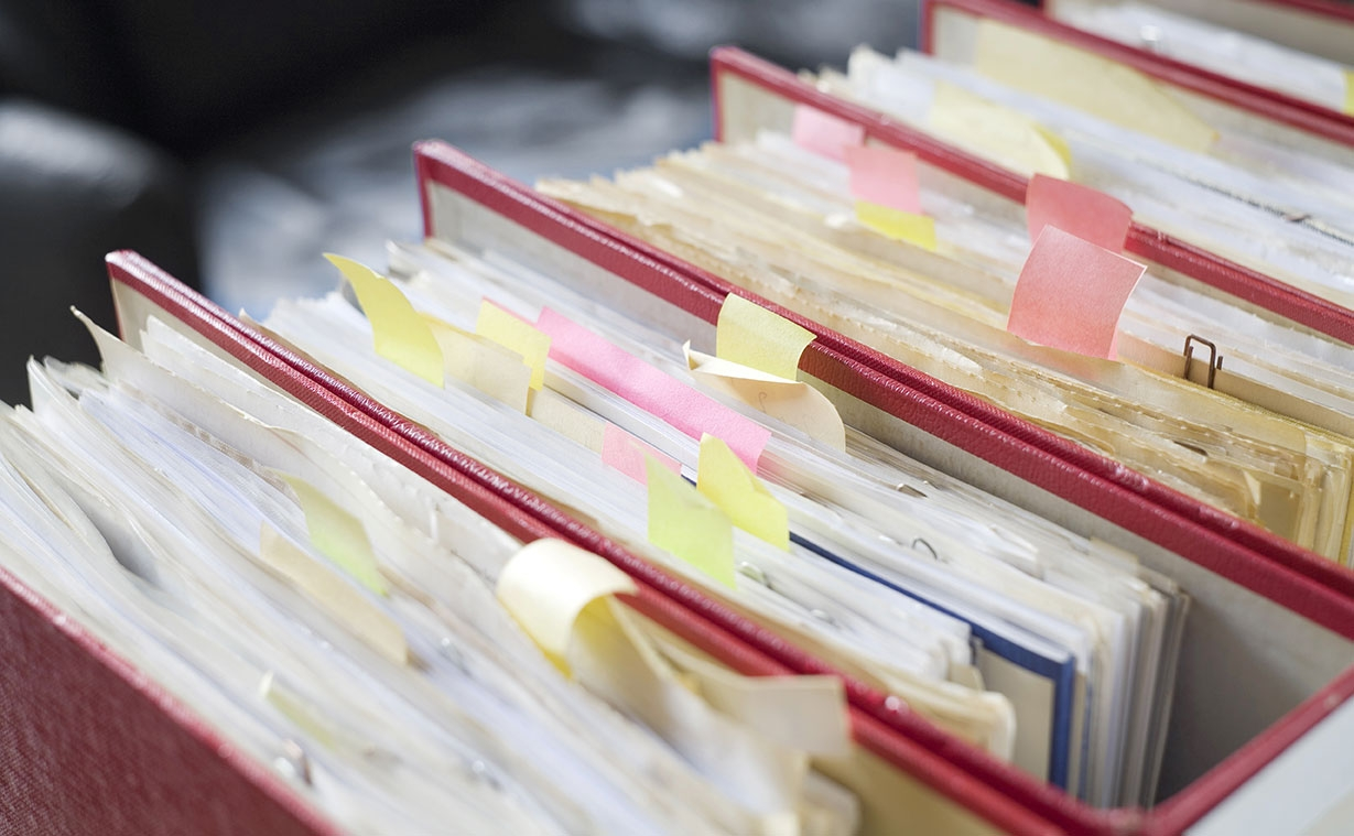 A filing system drawer opened and full of documents.