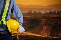 A miner wearing safety gear stands in front of an active work site.