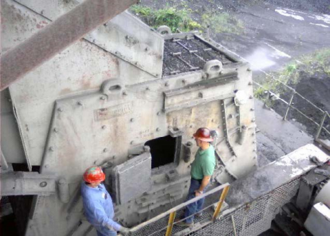 Two miners looking into a hatch