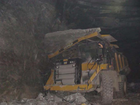 Haul truck covered in large fallen rock