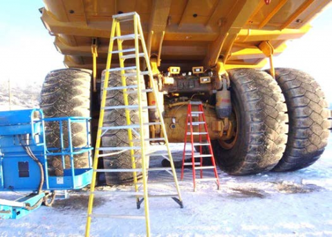 View from underneath a haul truck, four huge tires an plenty of room for a person to walk around