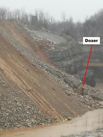Bulldozer at bottom of embankment close to water