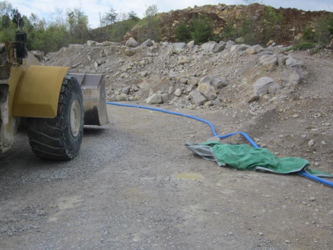 Corner of road with rocky ridge with loader