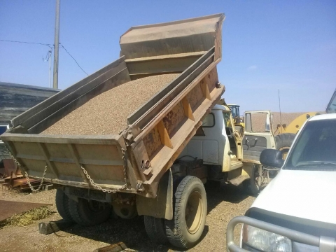 The dump truck with its bed shown in the raised position.