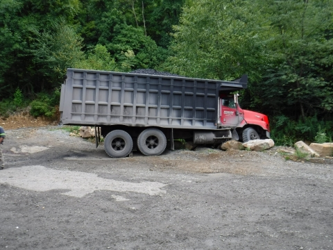 accident scene where a 53-year-old contract truck driver with ten years' experience was fatally injured while conducting a pre-operational examination of a truck.