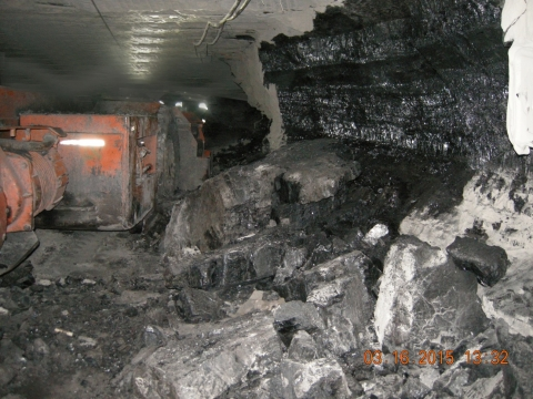 Accident scne where a 34-year-old section foreman with 10 years of mining experience was killed when a coal/rock rib approximately 90 inches long, 45 inches high, and 15 to 18 inches thick fell and pinned him against the side of a shuttle car.