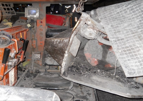 Accident scene where the miner was in the operator's compartment of his shuttle car, traveling through the last open crosscut, when a second shuttle car traveled through a ventilation curtain and struck his shuttle car.