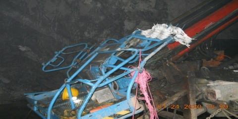 Accident scene where two miners were loading explosives from inside an aerial lift's basket when the basket jolted upward into the mine roof, causing the death of one of the miners.