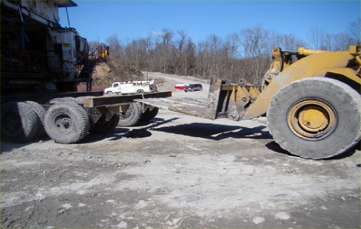 a miner transport dolly parked in front of a front-end loader. The arm of the loader is positioned within 2 feet of the back frame of the dolly.