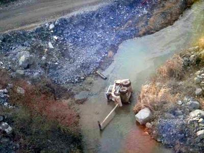 skid steer loader turned over in a ditch