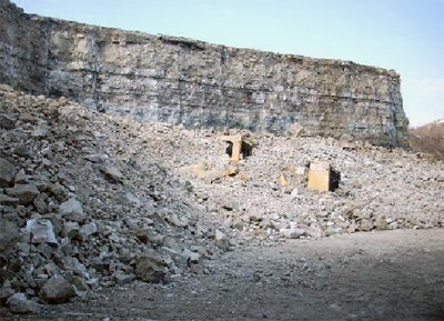 A front-end loader partially covered by rock after a blast