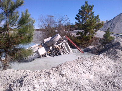 An overturned haul truck in a settling pond that is divided by a berm.