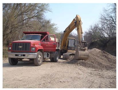 A truck parked beside the arm of the excavator. With the bucket of the excavator so close to the truck and knowing its angle of rotation, the photo shows how the bucket could have pinned the victim against the truck.