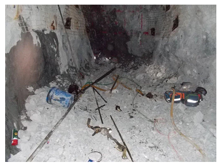 The work site of the victim. Numerous tools and other materials are scattered in the rocky corridor.
