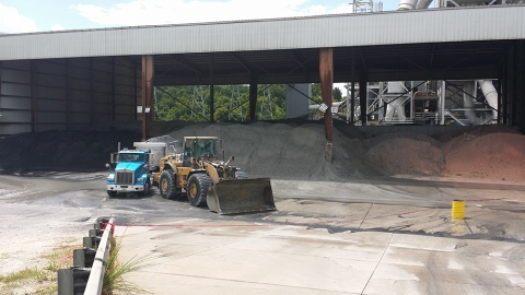 Wide angle of the accident site showing the positions of the truck and the front end loader. The truck is positioned with its rear facing the nearby ash mound for unloading and the loader has its rear diagonially against the truck
