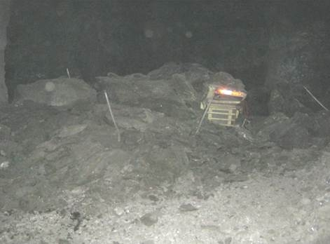 A mechanical scaler partially covered by debris from a mine roof fall.