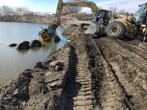 On a muddy shoreline, a crane positions its arm on a haul truck which is partially sunk into the water.