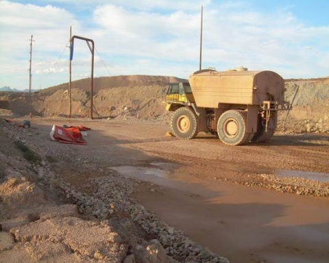 Crushed porta-john shown on left and water truck on right