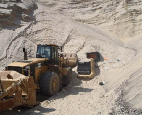 A front-end loader partially covered by a sand bank