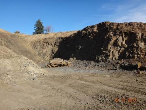 Bulldozer crumpled in pit from fall