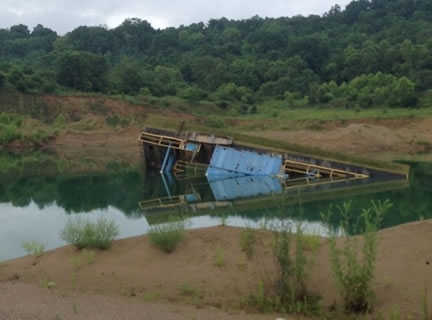 A partially submerged dredge after it capsized into the water.