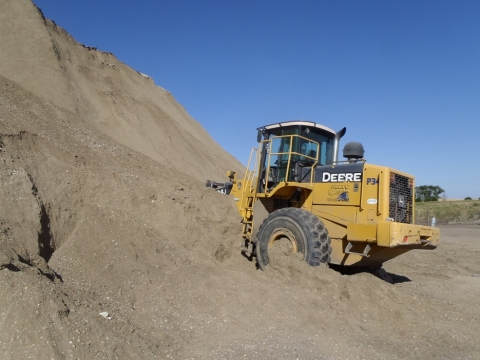 A front-end loader that is parked with its front against a sand bank