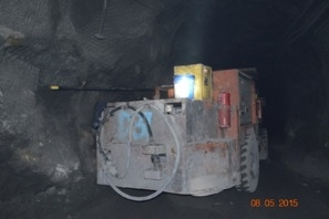 Underground and against a wall lies a machine cart with a long drill installed.