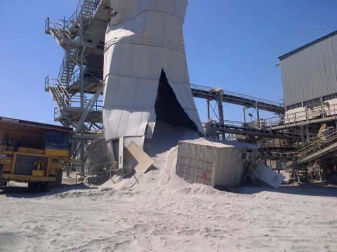 A sand silo that is cut on one side spilling debris