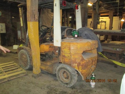 A forklift shown against a wooden support beam.