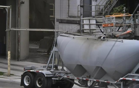 A bulk tanker truck with a metal rack hang over it.