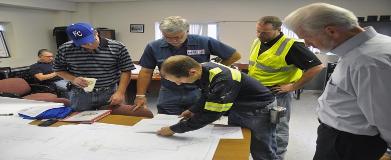 Company officials and MSHA personnel study a mine map in the mine office.