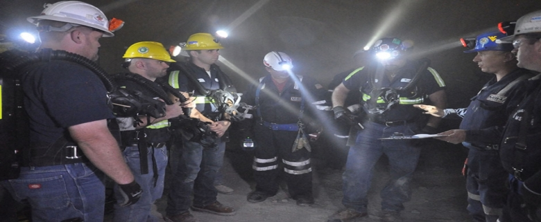A rescue team gathers underground and awaits instructions from its captain before proceeding.