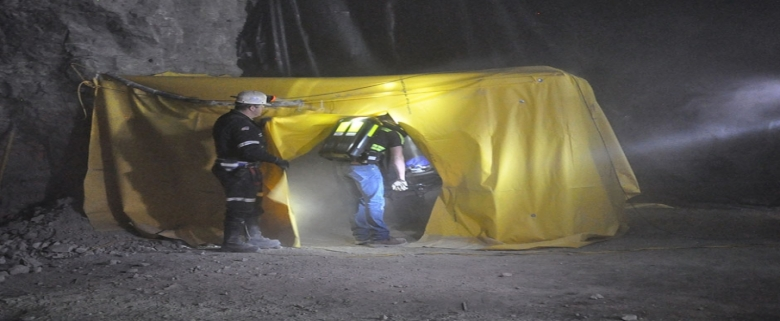 A smoke-filled atmosphere challenges mine rescue team members as they search for injured and trapped miners.